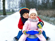 Little kid boy and cute toddler girl sitting together on sledge. Siblings, brother and baby sister enjoying sleigh ride royalty free stock photography