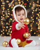 Little kid boy dressed as santa playing with christmas toys, dark background with illumination, happy new year and winter holiday. Concept Royalty Free Stock Photography