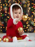 Little kid boy dressed as santa playing with christmas toys, dark background with illumination, happy new year and winter holiday. Concept Stock Photos