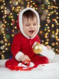 Little kid boy dressed as santa playing with christmas toys, dark background with illumination, happy new year and winter holiday. Concept Royalty Free Stock Photo
