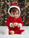 Little kid boy dressed as santa playing with christmas toys, dark background with illumination, happy new year and winter holiday. Concept Royalty Free Stock Images