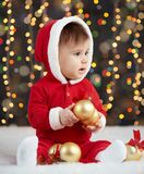 Little kid boy dressed as santa playing with christmas toys, dark background with illumination, happy new year and winter holiday. Concept Stock Images
