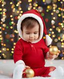 Little kid boy dressed as santa playing with christmas toys, dark background with illumination, happy new year and winter holiday. Concept Royalty Free Stock Photos