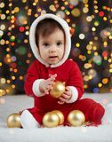 Little kid boy dressed as santa playing with christmas toys, dark background with illumination, happy new year and winter holiday. Concept Royalty Free Stock Image