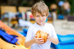 Little kid boy drinking coconut juice on tropical beach Royalty Free Stock Image