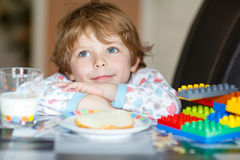 Little kid boy drinking milk and playing with construction block Royalty Free Stock Photos