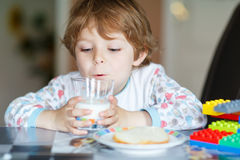 Little kid boy drinking milk and playing with construction block Royalty Free Stock Image