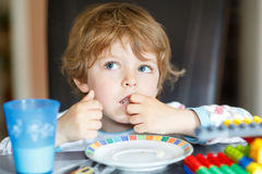 Little kid boy drinking milk and playing with construction block Royalty Free Stock Images