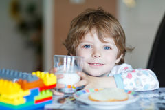 Little kid boy drinking milk and playing with construction block Stock Photo