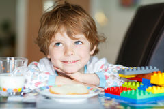 Little kid boy drinking milk and playing with construction block Royalty Free Stock Photography