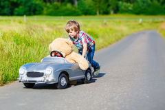 Little kid boy driving big toy car with a bear, outdoors. Stock Image