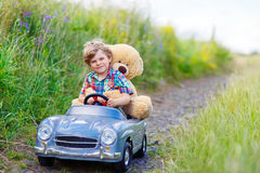 Little kid boy driving big toy car with a bear, outdoors. Little preschool kid boy driving big toy car and having fun with playing with his plush toy bear royalty free stock photo