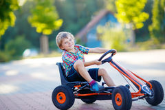 Little kid boy driving pedal race car in summer Stock Photo