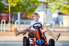 Little kid boy driving pedal race car in summer Royalty Free Stock Image