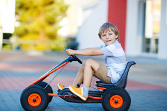 Little kid boy driving pedal race car in summer Royalty Free Stock Images