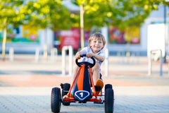 Little kid boy driving pedal race car in summer Stock Images