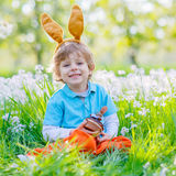 Little kid boy with Easter bunny ears and cupcake. Cute happy little boy wearing Easter bunny ears at spring green grass and blooming apple garden, eating Stock Image