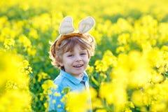 Little kid boy with Easter bunny ears in rape field Royalty Free Stock Photo
