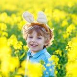 Little kid boy with Easter bunny ears in rape field Royalty Free Stock Photos