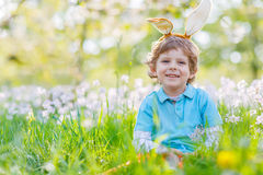 Little kid boy with Easter bunny ears in spring. Cute happy little kid boy wearing Easter bunny ears at spring green grass and blooming apple garden, laughing Royalty Free Stock Photography