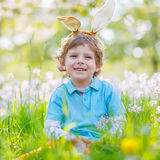 Little kid boy with Easter bunny ears in spring. Cute happy little kid boy wearing Easter bunny ears at spring green grass and blooming apple garden, laughing Royalty Free Stock Images