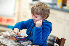 Little kid boy eating cereals for breakfast Stock Images