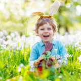 Little kid boy eating chocolate Easter bunny Stock Photography
