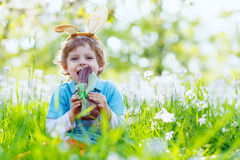 Little kid boy eating chocolate Easter bunny Stock Photos