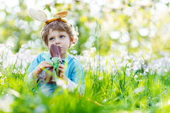 Little kid boy eating chocolate Easter bunny outdoors Royalty Free Stock Photos