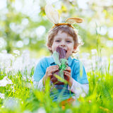Little kid boy eating chocolate Easter bunny outdoors Royalty Free Stock Image