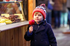 Little kid boy eating crystalized apple on Christmas market Stock Image