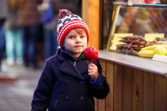 Little kid boy eating crystalized apple on Christmas market Royalty Free Stock Photography