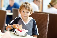 Little kid boy eating ice cream in outdoor cafe or restaurant. stock image