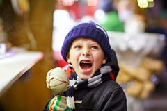 Little kid boy eating sugar apple sweets stand on Christmas market Stock Photography