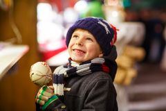 Little kid boy eating sugar apple sweets stand on Christmas market Royalty Free Stock Image