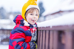 Little kid boy eating and tasting snow, outdoors on cold day Royalty Free Stock Photos