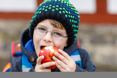 Little kid boy with eye glasses walking from the school and eating apple Royalty Free Stock Photos