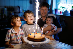 Little kid boy and family, father, brother and baby sister celebrating birthday. Adorable happy little kid boy celebrating his birthday. Child blowing candles on royalty free stock photography