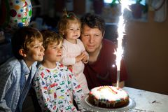 Little kid boy and family, father, brother and baby sister celebrating birthday. Adorable happy little kid boy celebrating his birthday. Child blowing candles on stock photo