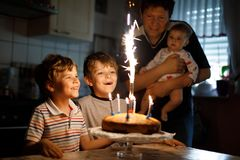 Little kid boy and family, father, brother and baby sister celebrating birthday. Adorable happy little kid boy celebrating his birthday. Child blowing candles on royalty free stock image