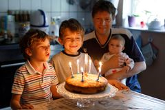 Little kid boy and family, father, brother and baby sister celebrating birthday. Adorable happy little kid boy celebrating his birthday. Child blowing candles on royalty free stock photo