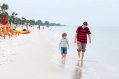 Little kid boy and father having fun with collecting shells. Adorable active little kid boy and his father having fun on Naples beach, Florida. Happy cute child Stock Images