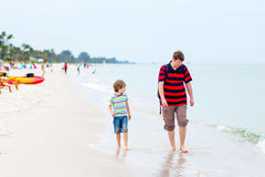Little kid boy and father having fun with collecting shells Royalty Free Stock Photography