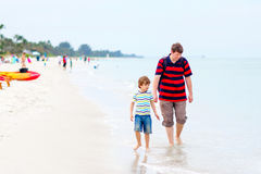 Little kid boy and father having fun with collecting shells. Adorable active little kid boy and his father having fun on Naples beach, Florida. Happy cute child Royalty Free Stock Photography