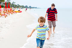 Little kid boy and father having fun with collecting shells. Adorable active little kid boy and his father having fun on Naples beach, Florida. Happy cute child Royalty Free Stock Images