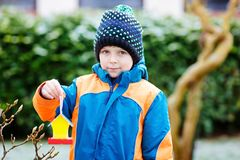 Little kid boy hanging bird house on tree for feeding in winter Stock Images