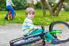 Little kid boy fell down of his first bike Royalty Free Stock Image