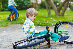 Little kid boy fell down of his first bike Stock Images