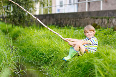 Little kid boy fishing on river with selfmade fishing rod Stock Images