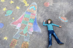 Little kid boy flying by a space shuttle chalks picture Royalty Free Stock Image